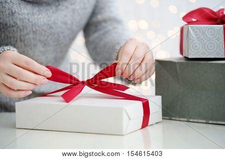 Close Up Shot Of Hands Wrapping Xmas Gift At Table.