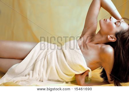studio shot, woman body covered with white towel