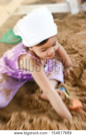 de-focused close up Asian little girl playing on sand