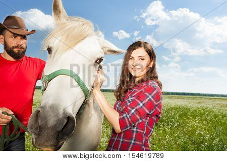 Young couple standing with their purebred white horse on a rural farm in summer