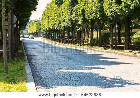Paris France - Jul 14 2014: large paved tree-lined road with no traffic near the fields Elysees avenue