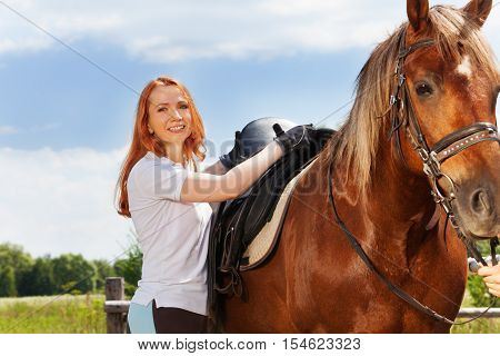 Beautiful smiling woman saddling a chestnut brown horse standing next to the enclosure at sunny day