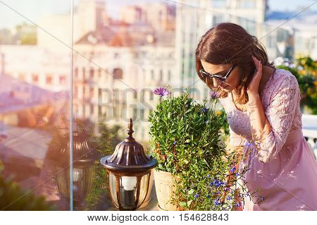 beautiful young woman in sunglasses smelling the flowers in cafe.