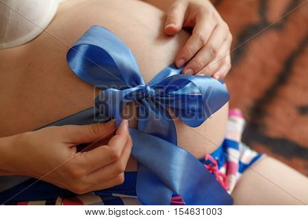 Pregnant woman. Belly with blue ribbon closeup. Third trimester of pregnancy