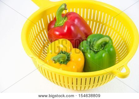 red, yellow and green sweet pepper in yellow basket. isolated on white background