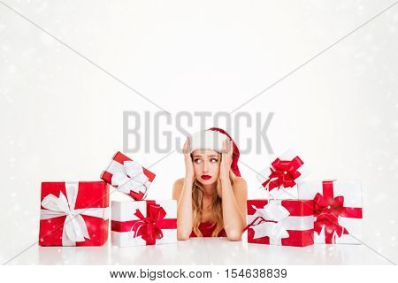 Sad upset young woman in santa claus costume with gift boxes over white background