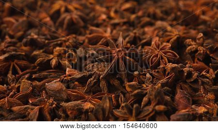 Background texture of star anise fruits and seeds. Spices and herbs pattern, closeup selective focus