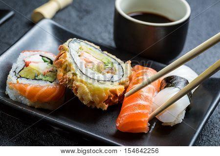Closeup of sushi eaten with chopsticks on black rock