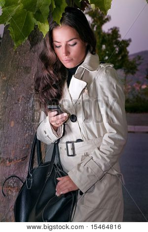 young woman calls from mobile phone, outdoor shot