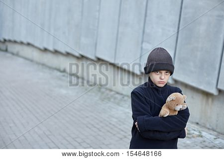 little homeless boy holding a teddy bear specifically biased composition poverty city street