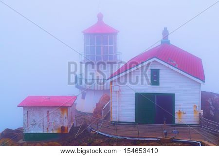 Historic Pt Reyes Lighthouse in the fog which is a historical landmark built in 1870 taken in Pt Reyes, CA