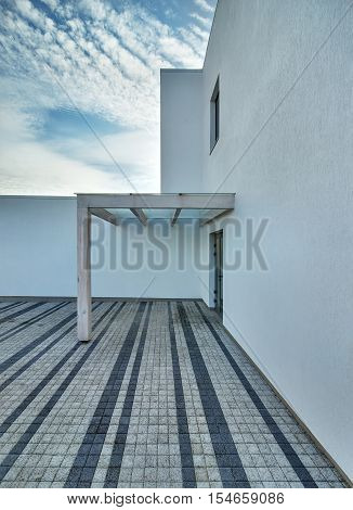 Entrance to the country house in a modern style on the sky with clouds background. There is a wooden-glass shed in front of the entrance and a tiled area. Outside. Vertical.