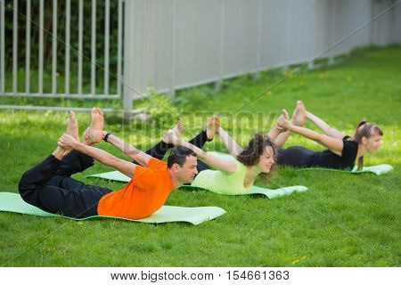 Man and two smiling women practice yoga on grass near fence at summer day