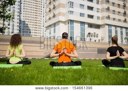 Man and two women practice yoga on grass near buildings at summer, back view