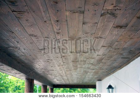 the ceiling is lined with wooden planks in porch of building