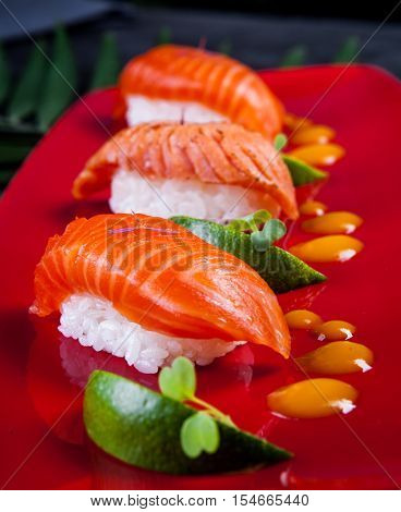 Sushi on red plate served with lime.