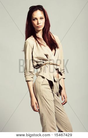 red hair woman in elegant leather blazer and pants, studio shot