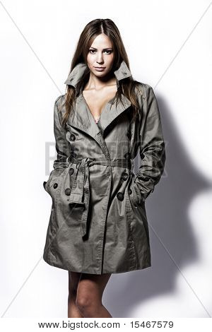 young brunette woman in topcoat studio shot on white