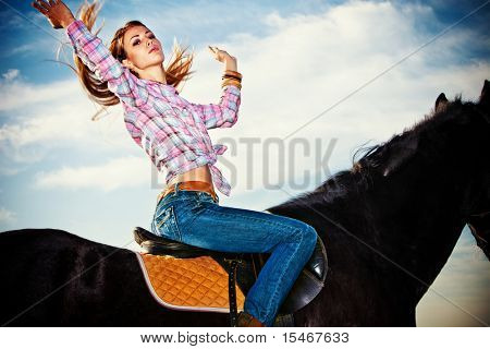 young woman on a horseback sky in background
