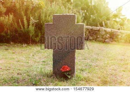 Sunny tomb with red flower next to the stone cross