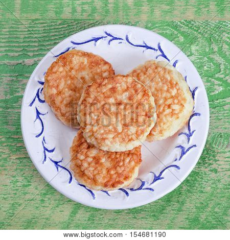 Rice patties in a plate on old wooden background.