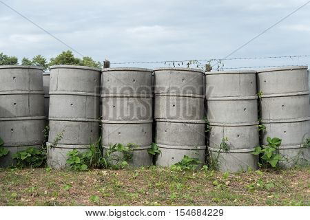 Concrete septic tanks stacked outdoors.Cement pipes placed outside