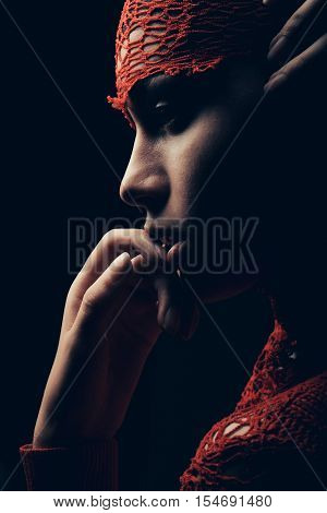 sexy young woman or cute girl with tender arm touch lips and pretty natural face profile wrapped in red knitted fashionable shirt on dark background close up