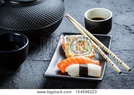 Sushi served with tea on black rock