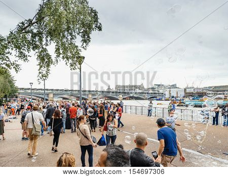 LONDON UNITED KINGDOM - JUL 9 2016: Group of people having fun with soap bubbles next to MOMA museum next to Thames riverbank - best adventure and vacancy in United Kingdom