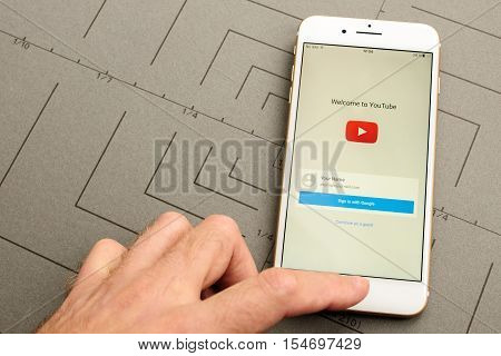 PARIS FRANCE - SEPT 26 2016: New iPhone 7 Plus with hand touching screen to sign-in to Youtube video sharing social network. iPhone 7 and iPhone 7 plus is the most wanted phone worldwide