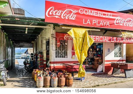 Livingston, Guatemala - August 31 2016: Looking through alleyway to dock next to riverside convenience store in afternoon light in Caribbean town of Livingston