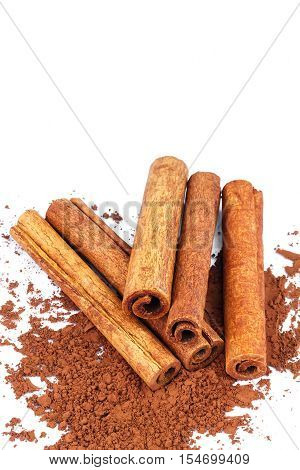 Group of cinnamon sticks on cacao powder isolated on white background close-up