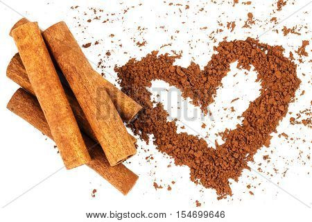 Cinnamon sticks and cacao powder in shape of heart isolated on white background top view close-up