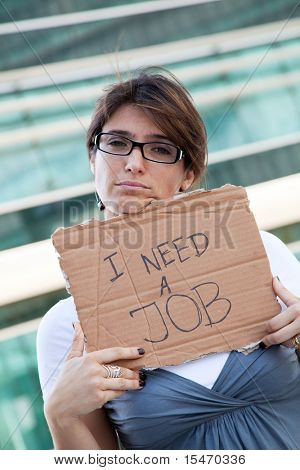 unemployed woman showing a message in a cardboard that she needs a job