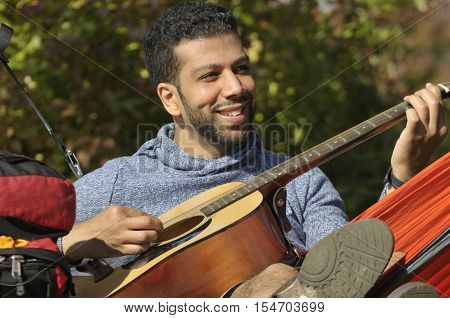 Happy young hispanic man composing music with a guitar in a hammock