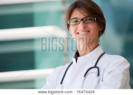 Friendly female doctor smiling to you next to a clinic