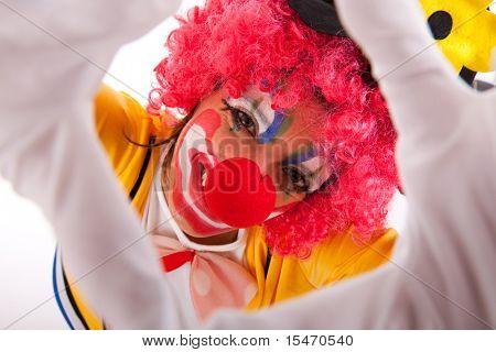funny clown peeking between his fingers (hand framing)