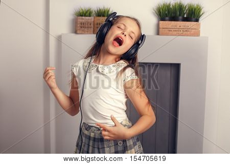 child rocker singing and dancing with headphones. The concept of lifestyle and music.