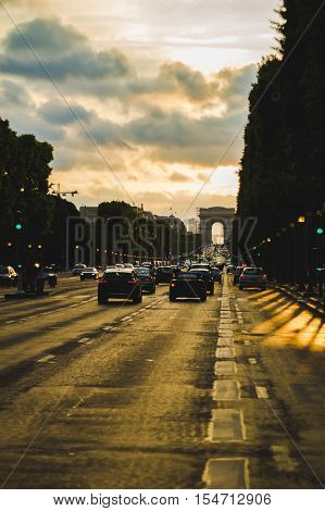 Cars driving down Av. des Champs-Élysées towards arc de triomphe at dusk