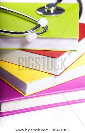 medical equipment and a stack of books isolated on white (selective focus)