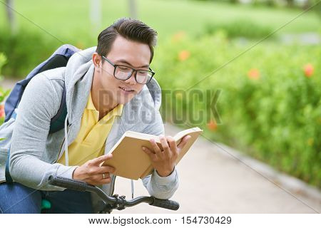 Asian student concentrated on book when sitting on bicycle