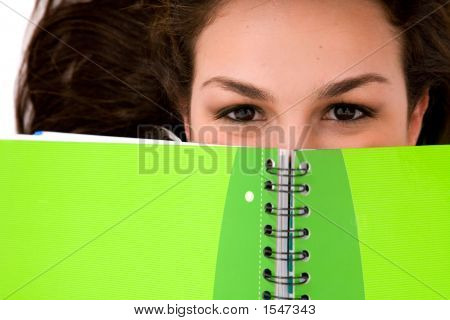 Beautiful Female Student Peeping Over A Green Notebook