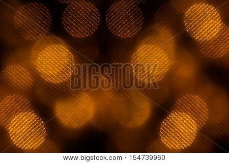 Bokeh dark orange mesh circles on black background. Abstract festive background.