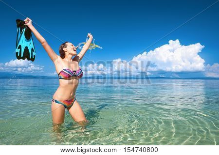 happy woman with a mask for snorkeling on a background of blue sea and islands. Beach holiday vacation woman snorkeling fun. Joyful happy woman wearing snorkeling equipment