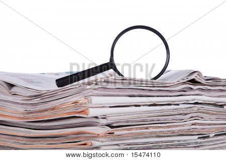 Magnify glass over a stack of newspaper to find fresh information (isolated on white)