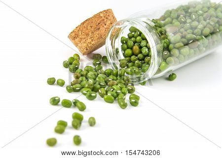 close up the green mung beans in glass bottle on white background