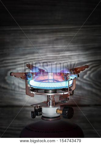 Burning portable gas burner on wooden background