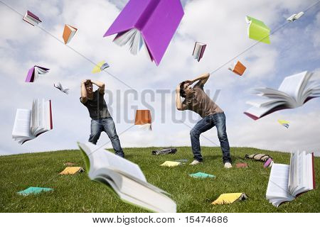 Teenager students outside protecting there heads from a rain of books
