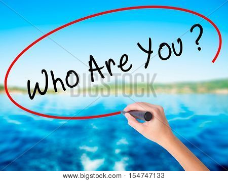 Woman Hand Writing Who Are You With A Marker Over Transparent Board