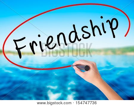 Woman Hand Writing Friendship With A Marker Over Transparent Board
